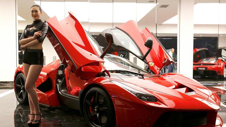 Een model poseert met een Ferrari LaFerrari. Beeld epa