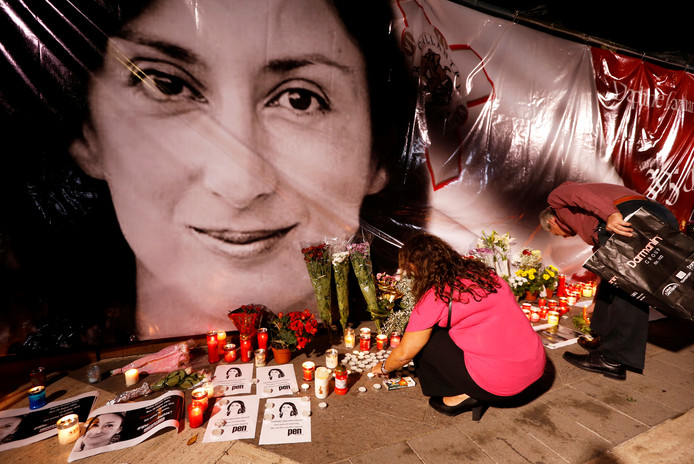 Mensen leggen bloemen en branden kaarsen bij een afbeelding van de vermoorde Daphne Caruana Galizia.