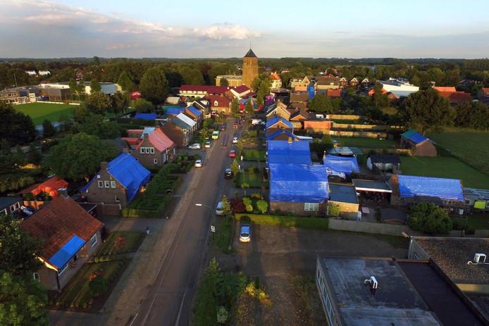 Een luchtfoto van Luyksgestel die de zondag na de hagelstorm van donderdag werd gemaakt, laat zien hoe groot de schade is. Vrijwel alle daken zitten vol gaten en zijn daarom afgedekt met blauwe en oranje zeilen.