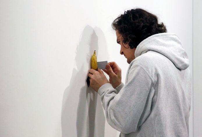 Un employé de la galerie Perrotin ajuste la position de la banane contre le mur où elle est exposée.