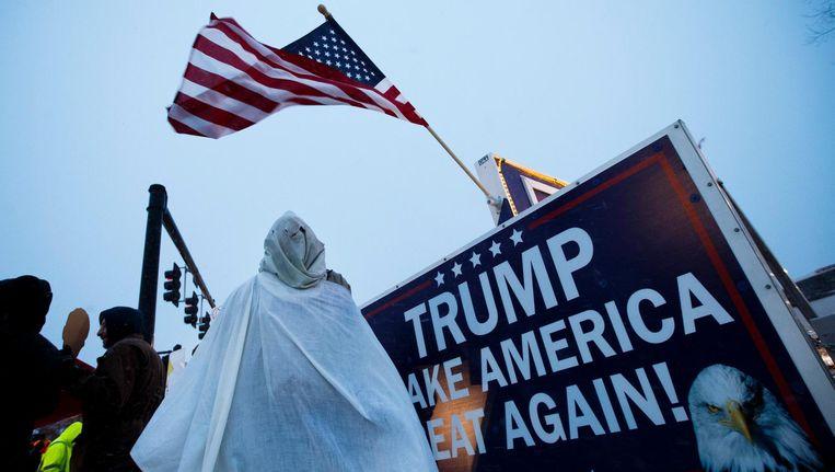 Een demonstrant met een imitatiegewaad van de KKK bij een Trump-bijeenkomst