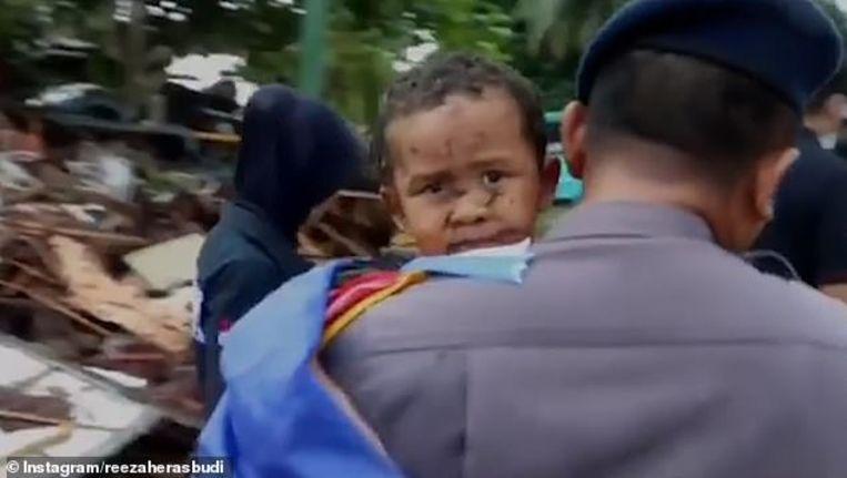 De kleine Ali wordt weggedragen door een agent.