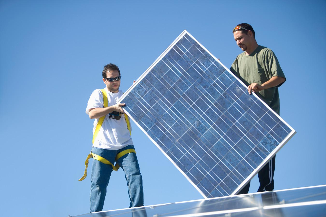 Two men lifting a solar panel stockadr zonnepaneel zonnepanelen zonne-energie groene energie duurzame