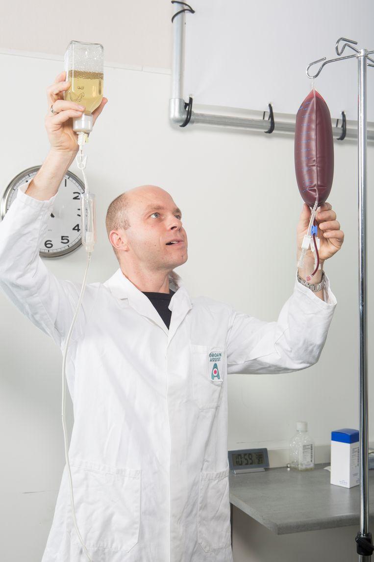 Martin Kuizenga, van Organ Assist, controleert varkensbloed dat door het hart zal worden gepompt. Beeld Niels Blekemolen