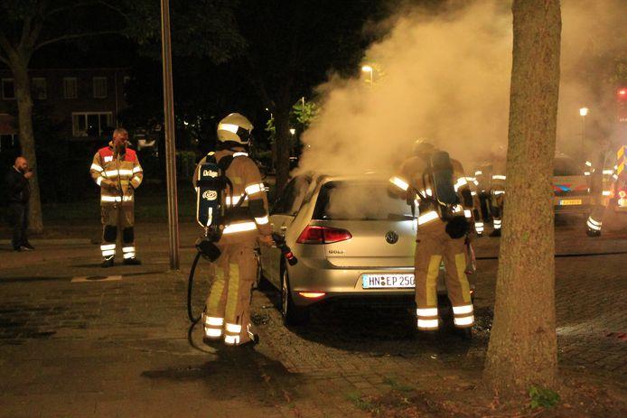 De brandweer in actie  bij de autobrand n de Utrechtse wijk Zuilen.