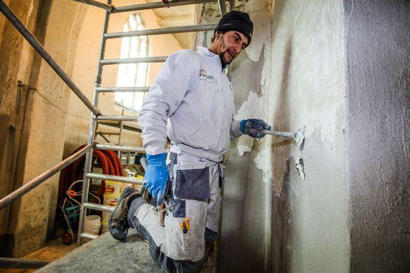 Meetkerke de kerk wordt herschilderd: de verf wordt van de muur geschraapt