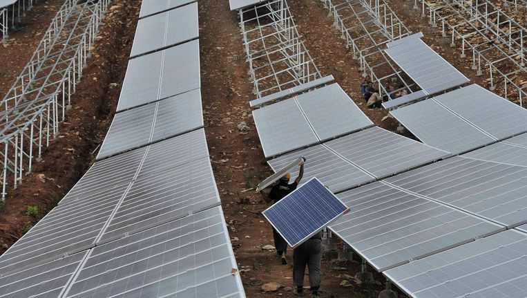 Op een heuvel bij het Chinese Wuhu worden panelen op stellages gelegd voor een enorme zonneweide. Beeld REUTERS