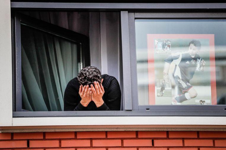 Mohammed, de broer van Nouri, hangt aangeslagen uit het raam van het huis van de Ajacied, op de dag dat fans samenkwamen bij de woning in Geuzenveld Beeld anp