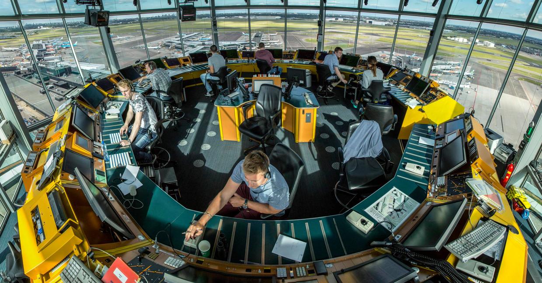 Luchtverkeersleiders aan het werk in de toren op Schiphol. Beeld Feike Westenbroek
