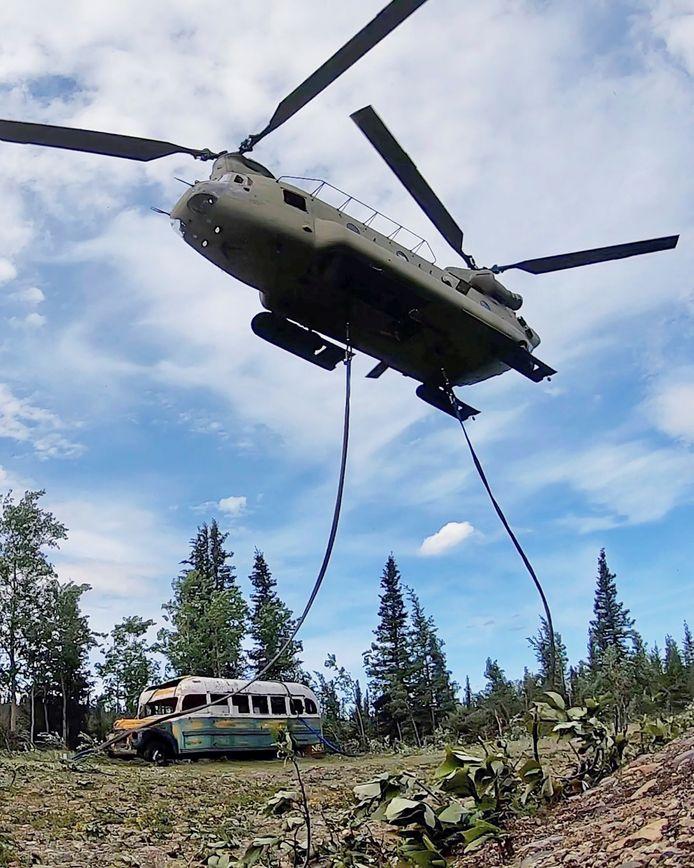 """Un hélicoptère CH-47 Chinook de la garde nationale de l'armée de l'Alaska transporte le bus rendu célèbre par le livre et le film """"Into the Wild"""" lors de son transfert près de la piste du Stampede à l'ouest de Healy, Alaska, aux États-Unis, le 18 juin 2020."""