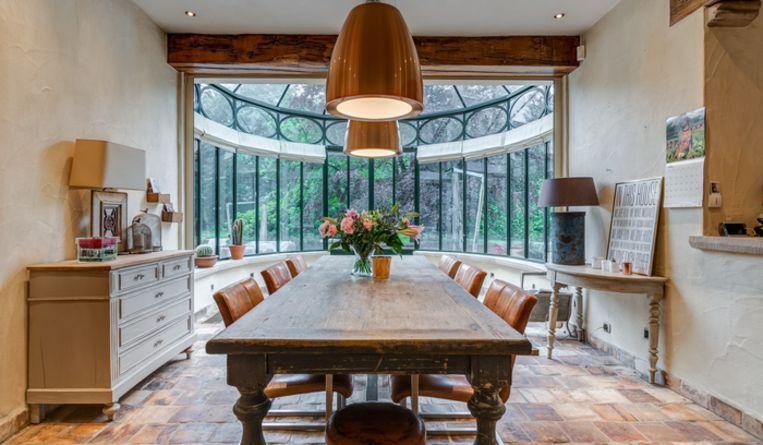 Deze gezellige zitplaats met aanpalende veranda biedt uitzicht op de imposante tuin.
