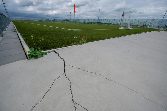 Scheuren in het beton rond het veld.