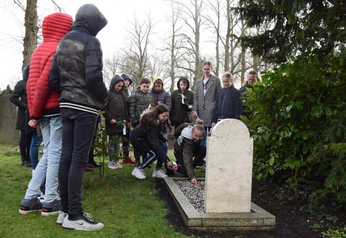 Scholieren van groep 8 van de Montessorischool De Pas bij een van de geallieerde graven aan de Loolaan.