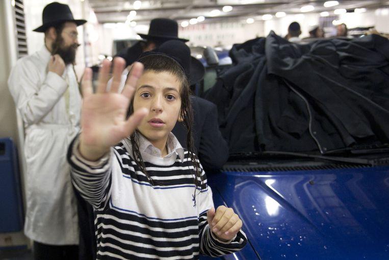Rabbijn Eliezer Berland wordt afgeschermd door zijn volgelingen en zit in een afgedekte auto op de veerboot van Texel naar Den Helder. De Israelische rabbijn, die in eigen land wordt verdacht van ontucht, verbleef met 300 aanhangers op een Texelse camping. Beeld ANP