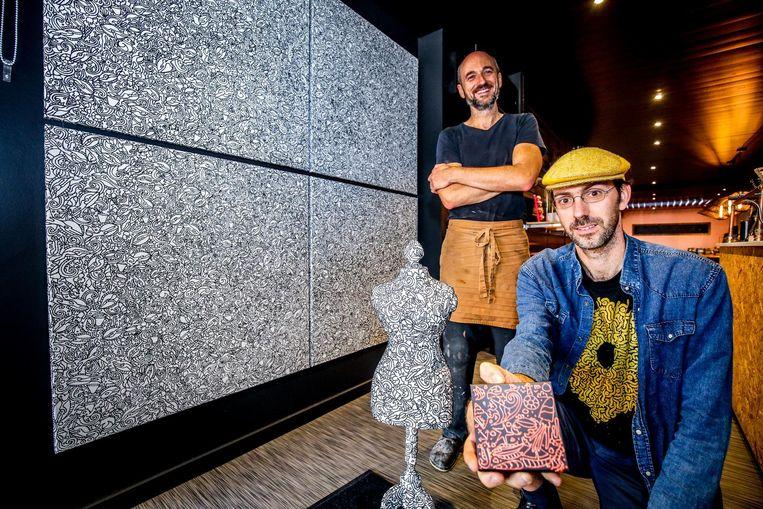 Kunstenaar David Maertens en bakker Peter Bossier met een tegel en paspop van chocolade.