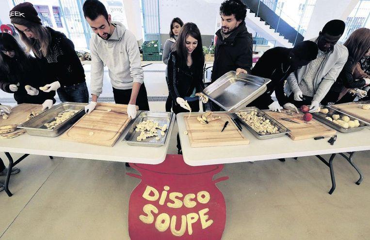 'DiscoSoep' is inmiddels een wijdverbreid verschijnsel: jongeren, zoals hier in het Franse Reims, koken met overgebleven voedsel en eten dat daarna ook samen op. Beeld anp