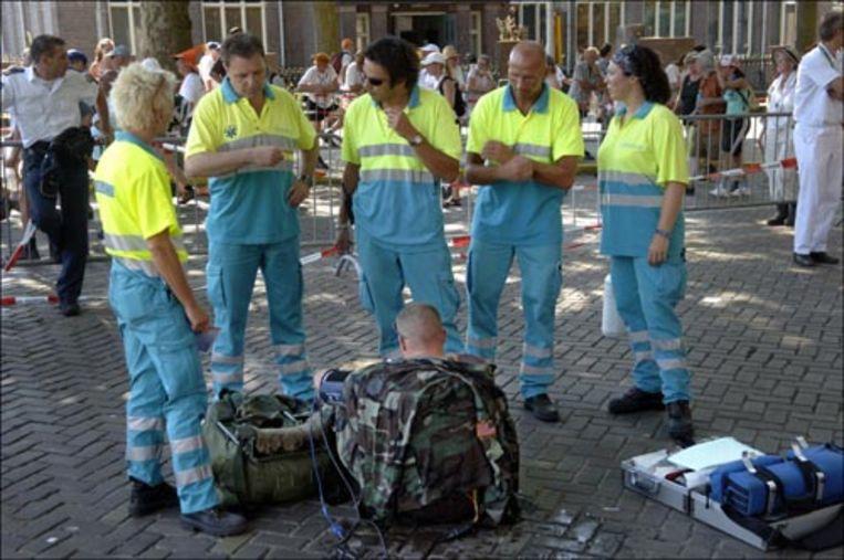 Ambulancepersoneel overlegt dinsdag tijdens de Vierdaagse in Nijmegen bij een militair die aan medische meetapparatuur ligt. Het wandelevenement is afgelast na de dood van twee mensen op de eerste dag. (ANP) Beeld ANP