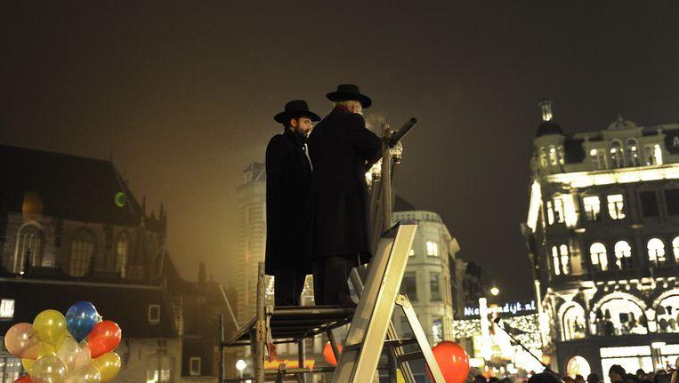 Archieffoto. Een rabijn steekt de rest van de kaarsen aan, nadat burgermeester Van der Laan de eerste kaars van een zevenarmige kandelaar (menora) heeft aangestoken op de Dam in Amsterdam. Beeld ANP