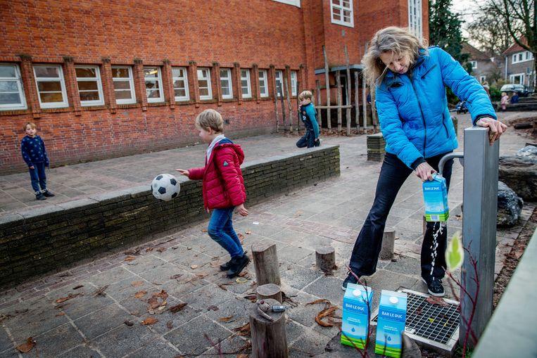Bewoners tappen water bij de pomp op het Wognumerplantsoen in Nieuwendam. Beeld Jean-Pierre Jans