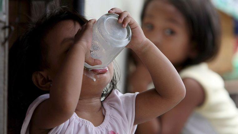 Een Filipijns meisje drinkt melk. Beeld ANP