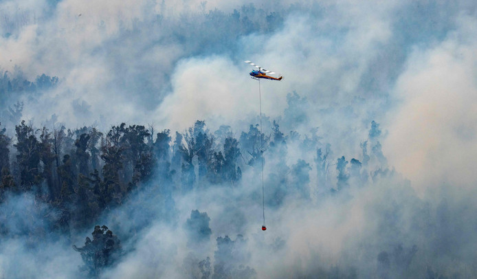 Een helikopter dropt water in brandend gebied