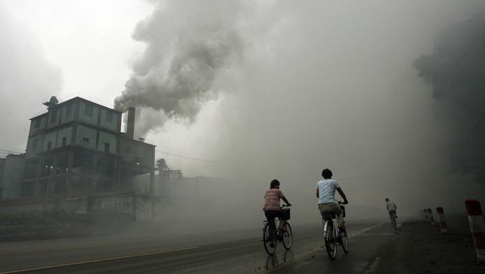 Des cyclistes passent devant une usine à Yutian, à 100km de Pékin, en Chine.