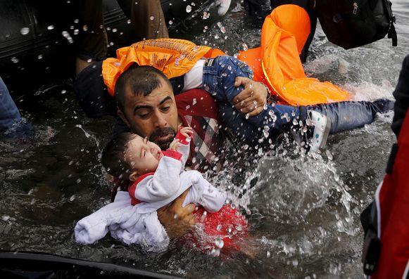Een Syrische vluchteling houdt zijn kinderen vast om van een rubberboot op het Griekse eiland Lesbos te lopen.