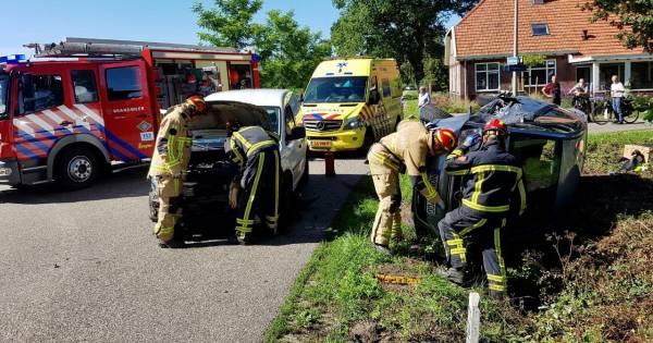 Frontale botsing in Mander: Auto op zijn kant en twee gewonden.