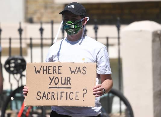 Een demonstrant die een gezichtsmasker draagt, houdt een protestbord vast voor het huis van Dominic Cummings.