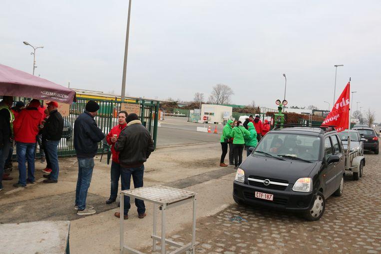 De stakers blokkeren met personenwagens de uitrit bij Verko zodat vuilniswagens niet uit kunnen rijden.