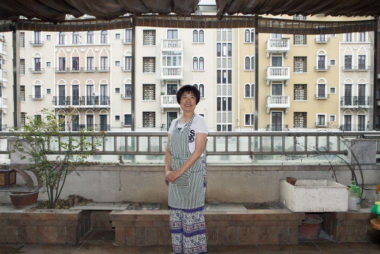 Zhu Yanming op het balkon van haar appartement in Waterstad. Beeld Ruben Lundgren