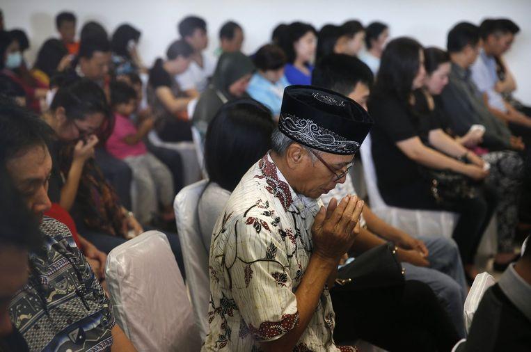 Familieleden van passagiers van vlucht QZ8501 bidden gezamenlijk in een wachtruimte van het vliegveld van Surabaya. Beeld reuters