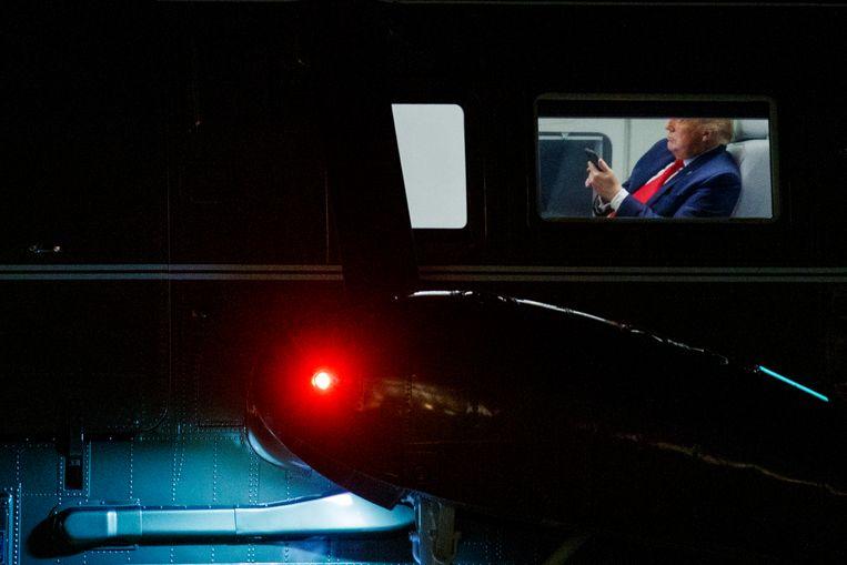 De Amerikaanse president Donald Trump kijkt op zijn telefoon terwijl zijn helikopter Marine One bij het Witte Huis in Washington landt.  Beeld EPA