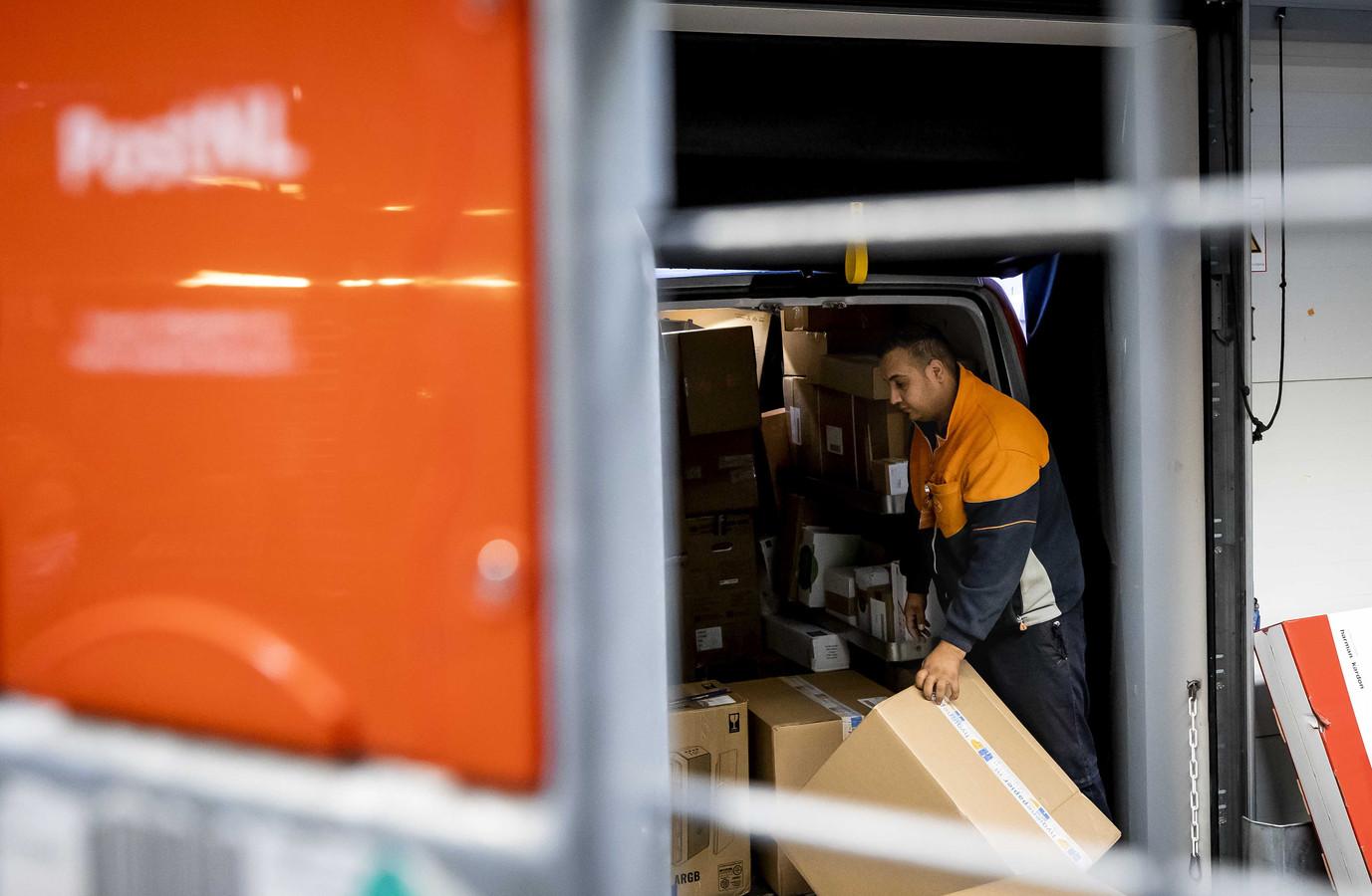 Medewerkers van post- en pakketbezorger PostNL sorteren pakketjes in het pakkettensorteercentrum. In aanloop naar Black Friday, Sinterklaas en Kerst is dit een van de drukste periodes van het jaar. De medewerkers krijgen er structureel meer loon bij.