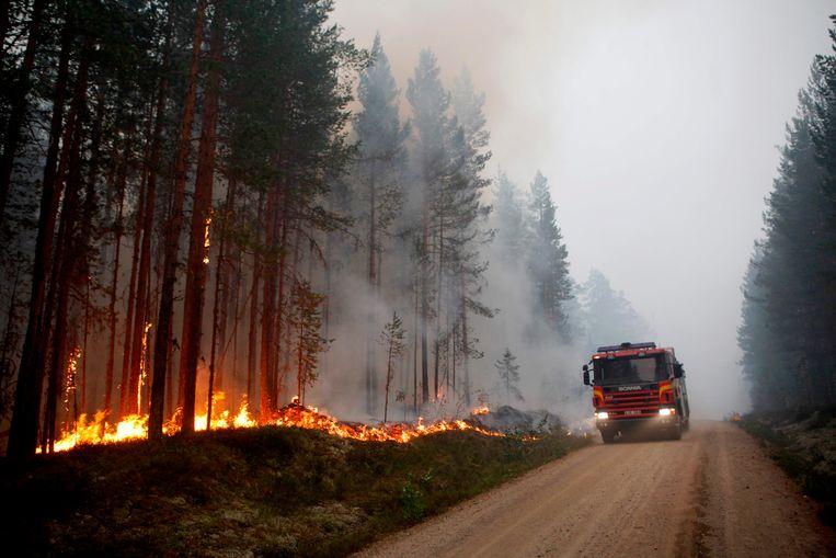Een brandweerwagen op een bosweg waar het brandt in Karbole, Sweden.