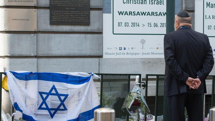 Een man staat bij het museum om de slachtoffers te herdenken.