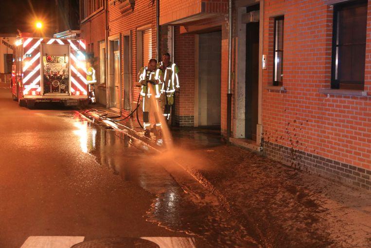 De brandweer spoot de bruine smurrie van het voetpad en de gevels.