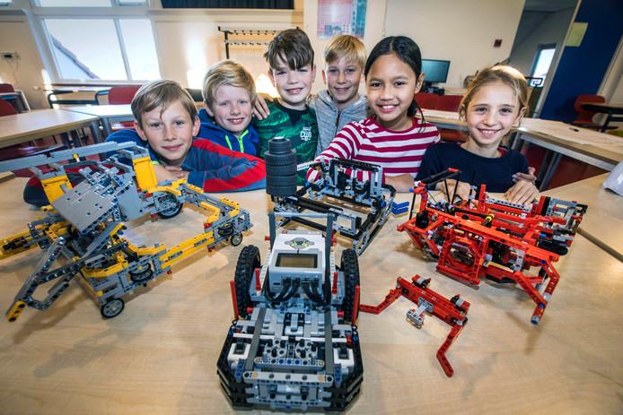 Mees, Marijn, Yannick, Enzo, Pramesthi en Feline (v.l.n.r.) bij hun robots in de Freinetschool.