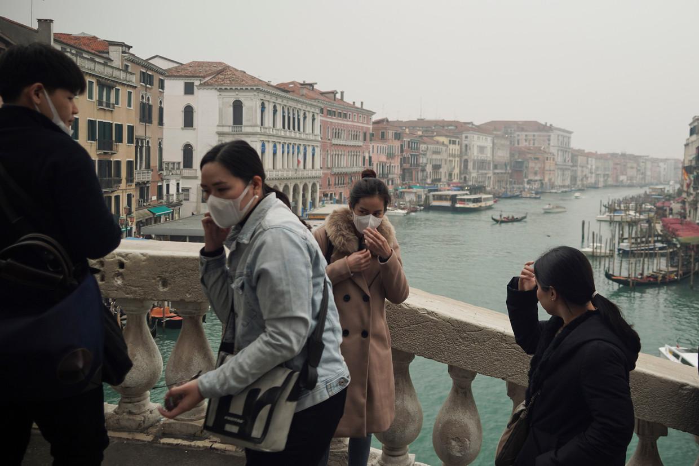 Toeristen nemen selfies op de Rialto brug in Venetië.  Beeld AP