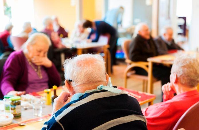 Ouderen aan tafel in een verzorgingshuis. De zorg moet beter, maar hoe?
