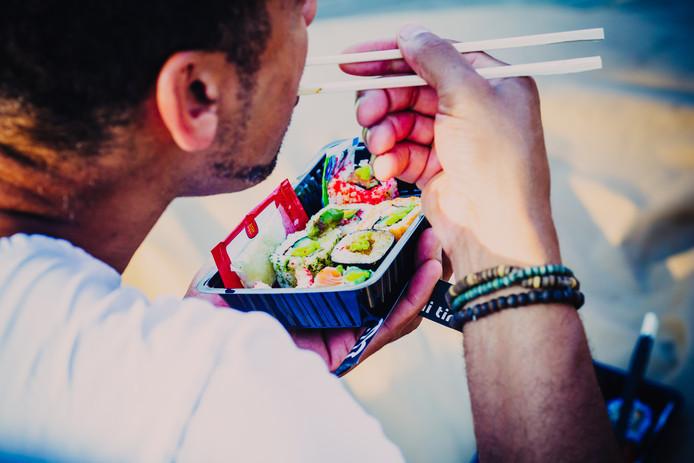 Een man geniet van sushi op JOY.