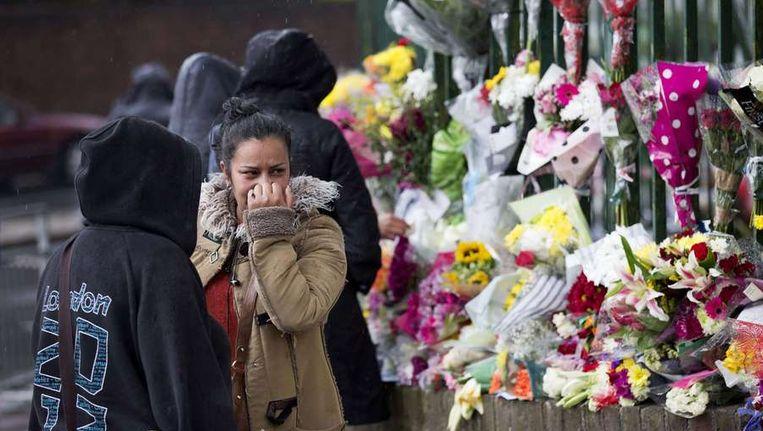 Een vrouw kijkt naar de bloemen die achtergelaten zijn op de plek waar Lee Rigby werd vermoord Beeld afp