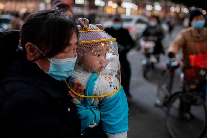 Een vrouw met haar baby in de Chinese miljoenenstad Wuhan, waar het coronavirus in 2019 voor het eerst opdook.