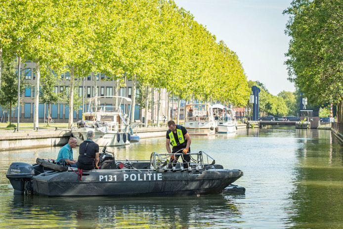 Politiemensen vissen met magneten naar het moordwapen van Richard Houtveen.