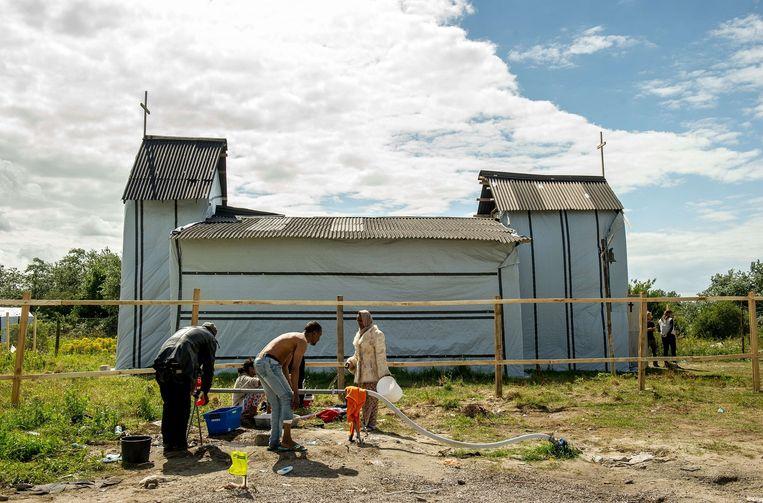 In de 'New Jungle' bouwen migranten zelf hun tenten. Er verrezen onder meer een kerk (bovenstaande foto) en een winkel (foto onder). Beeld afp