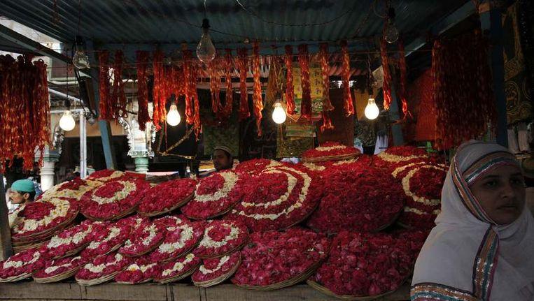 Verkopers van bloemen bij het graf van de heilige. Beeld reuters