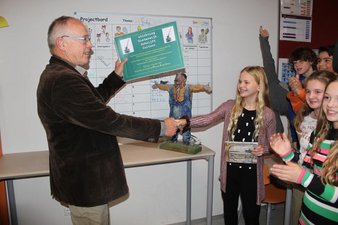 Dré van Hal, penningmeester van stichting Oisterwijk Schrijft Cultuur, reikt de schrijfprijs uit aan Sara Augustijn van basisschool de Bunders uit Oisterwijk.