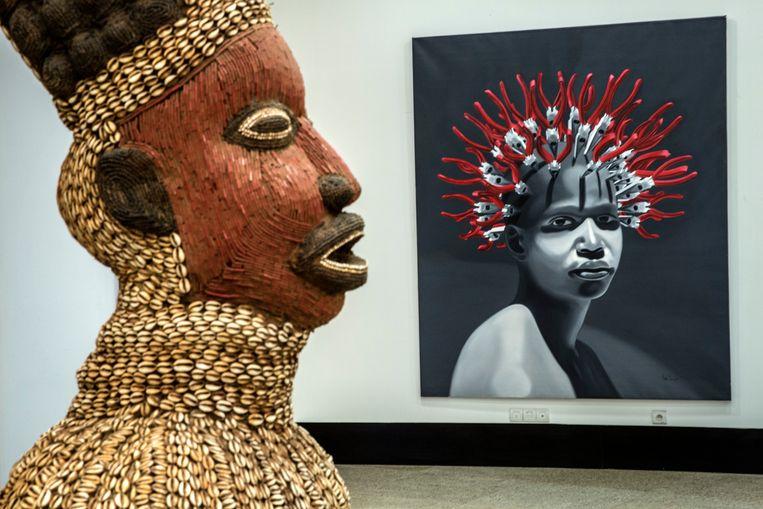 Links een antiek beeld uit Kameroen en rechts een schilderij uit 2018 van het Cubaanse kunstcollectief 'The Merger'. Beeld Hollandse Hoogte / The New York Times Syndication