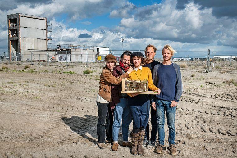 Toekomstige bewoners, onder wie Chandar van der Zande (tweede van links), met een maquette van De Warren.  Beeld Guus Dubbelman / de Volkskrant