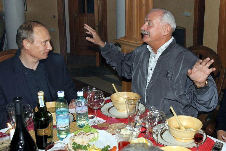 Poetin luistert naar Michalkov op het verjaardagsfeestje van de regisseur in 2005. Beeld AFP